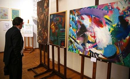 У стенда работ Андрея Мунца. Выставка в Доме Архитектора